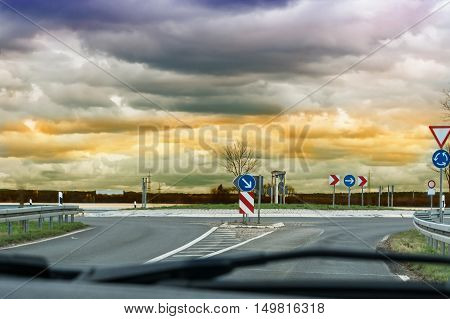 Looking through the windshield of a car on the road. When approaching a Car Roundabouts with dramatic sky in the background.