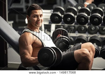 Pleasant workout in a gym. Handsome strong delighted sportsman leaning on a gym apparatus and lifting dumbbells while having a workout