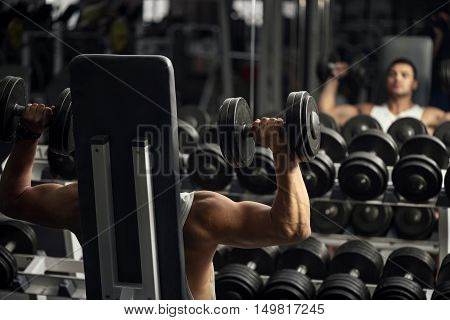 Impressed with strength. Serious persistent hard working male weightlifter sitting on a gym apparatus and lifting dumbbells while looking in the mirror