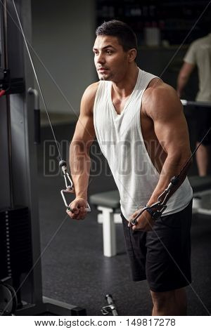 Physical stamina. Handsome athletic muscular sportsman straining his muscles and trying to put his arms together while doing a physical exercise