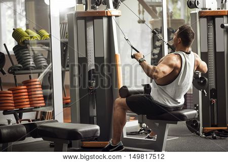 Develop your body. Good looking well built athletic man leaning backwards and pulling the weight on him while using a gym apparatus