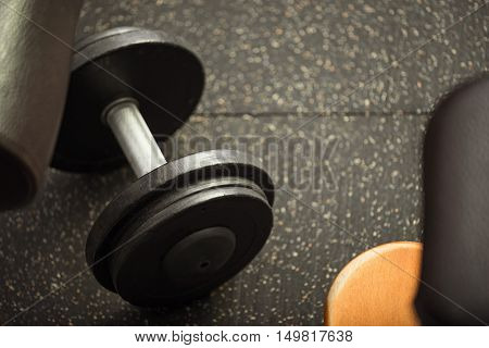 Sports equipment for weightlifters. Close up of a black metal heavy dumbbell lying on a gym floor
