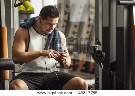 What song to choose. Strong well built young sportsman holding his MP3 player and choosing a song while sitting on a gym apparatus