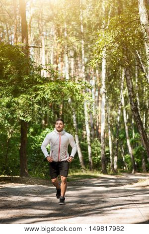 Pleasant surroundings. Nice good looking well built man enjoying nature and running on the road while spending time in the park