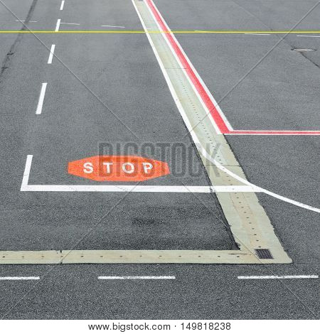 Airport runway and taxiway with marking and signs.