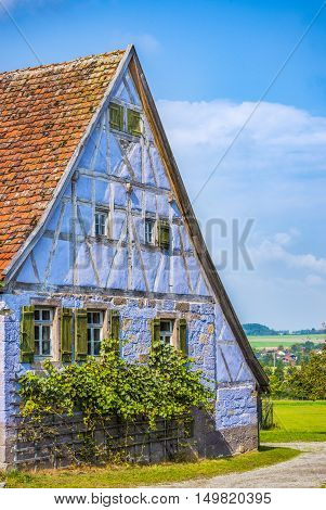 Medieval blue German traditional house  - Antique house with German specific architecture half timbered and stone walls of blue color windows with wooden shutters and tile gable roof.