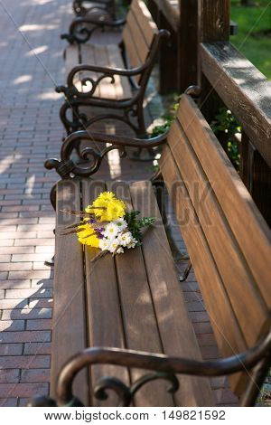 Bouquet on wooden bench. Flowers of bright color. Summer brings beauty. Simplicity and perfection.
