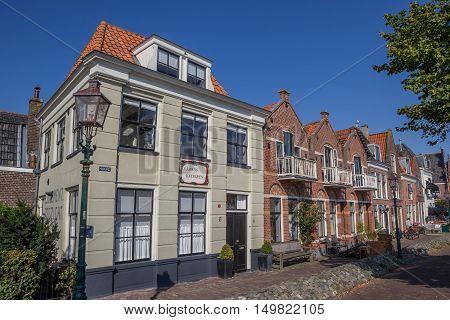 HOORN, NETHERLANDS - SEPTEMBER 13, 2016: Cobblestoned street with old houses in the harbor of Hoorn
