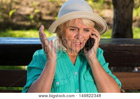 Nervous woman with phone. Senior lady wearing a hat. Must solve the problem. No one can help.