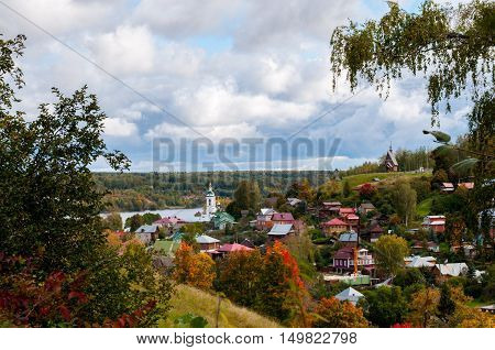 Bright autumn colors of the countryside in the small corner of a little town in Russia. The calm river is near the town.