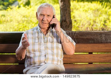 Senior guy on the phone. Elderly man sits on bench. Explain the whole situation. Not in mood for arguing.