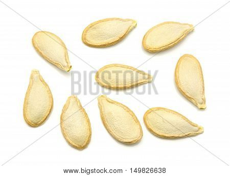 Top view of dried pumpkin seeds on a white background