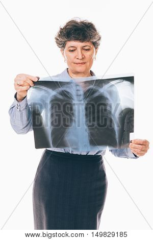Confused senior woman is examining lungs radiography holding it in front of her chest - isolated on white