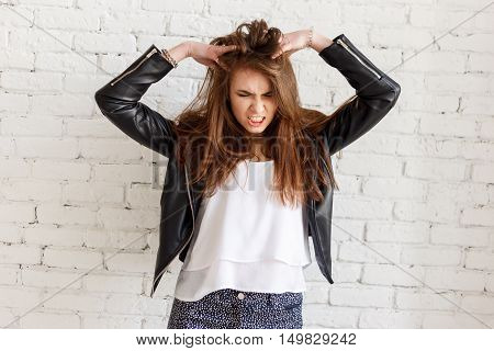 Woman stressed is going crazy pulling her hair in frustration.