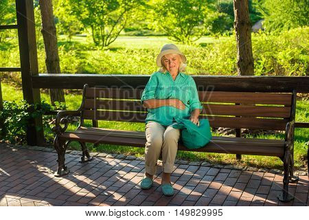 Mature woman has stomach ache. Lady in the park. I need medicine against pain. Illness grew into chronic.