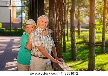 Smiling elderly man and woman. Senior couple near wooden fence. Build happiness together. Support and trust.