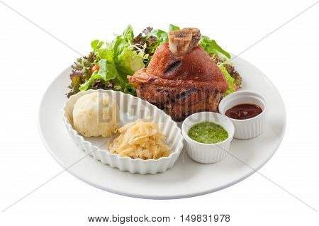 Front view of German Pork Hocks or pork knuckle with barbecue sauce Thai spicy sauce mashed potatoes pickled cauliflower and fresh vegetables in ceramic dish isolated on white backgrund