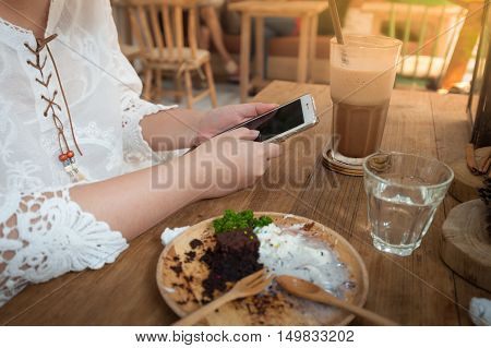 Weekend lifestyle scene of young woman using phone in cafe. Trendy lifestyle with technology concept
