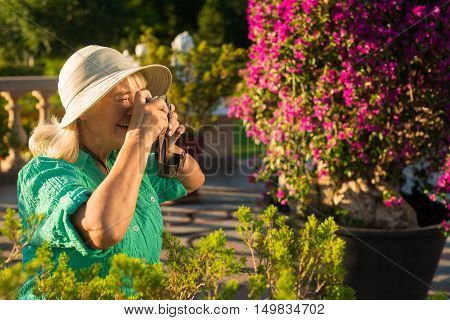 Senior woman with photo camera. Mature lady in summer hat. Interest and inspiration. Photographer captured landscape.