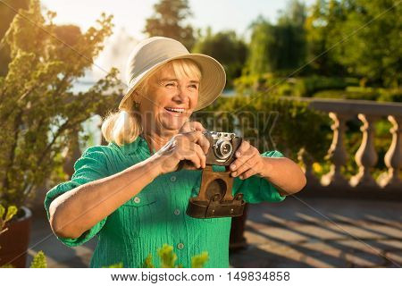 Smiling woman with camera. Senior lady in summer hat. Inspiration is easy to find. Photographer in good mood.
