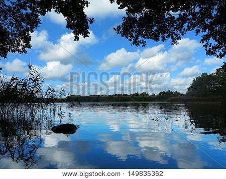 lonesome idyllic lake in beautiful natural landscape reflecting cloudy blue sky
