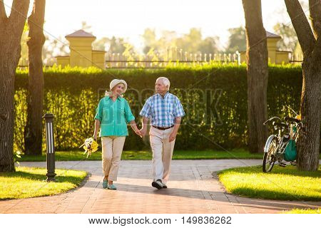 Senior couple walks on alley. Elderly people outdoors. We live a full life. Stay together and save love.