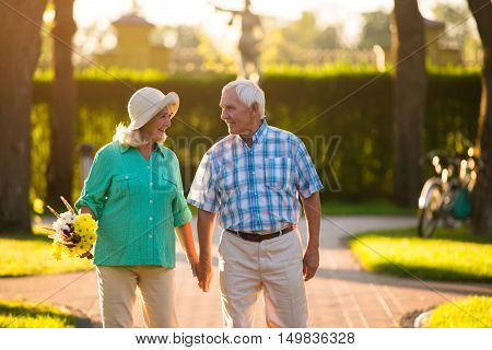 Senior couple is holding hands. Man and woman outdoor. Unity and happiness. Feelings are priceless.