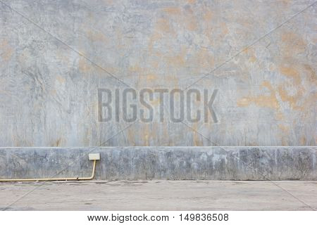 grungy mud dirty concrete wall background with yellow PVC pipe on the ground.
