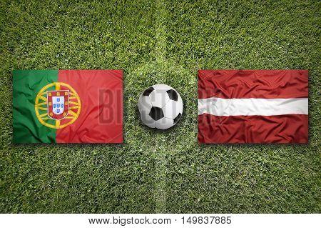 Portugal vs. Latvia flags on green soccer field, 3D illustration