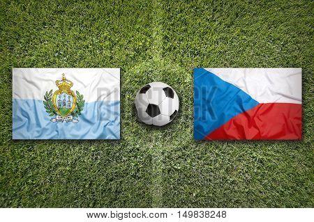 San Marino vs. Czech Republic flags on green soccer field, 3D illustration