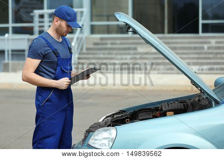 Mechanic with a clipboard and pen standing near open car hood
