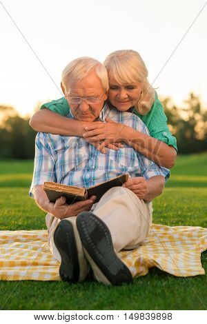 Senior couple reads book. Two people sitting on meadow. Our favorite story. Turn the page.