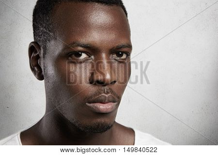 Сlose Up Portrait Of Young Confident Dark-skinned Man With Moustache And Small Beard, Dressed In Whi