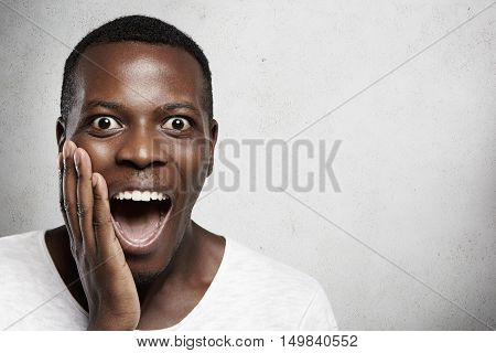 Human Face Expressions And Emotions. African Male Screaming In Surprise, Mouth Wide Open, Holding Ha