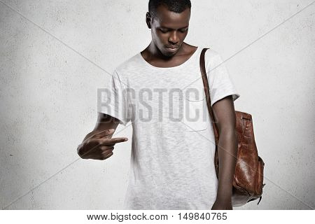 T-shirt Design And Advertising Concept. Indoor Portrait Of Fashionable Dark-skinned Young Male Point