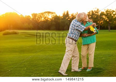 Elderly couple is kissing. Man and woman with flowers. Happy anniversary, darling. You're the best.
