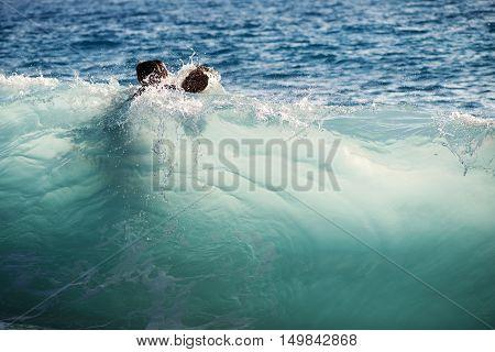 Unrecognizable people splashing in crystal clear blue sea water.
