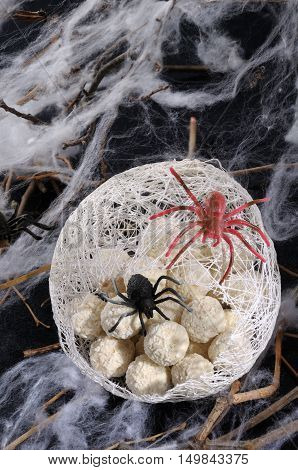 candy waffle balls in the form of spider eggs in a cocoon with a spider on the table for Halloween