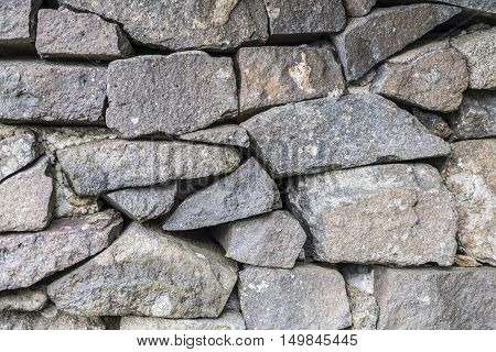 Ancient stone wall skilfully constructed with different shaped gray rocks to provide texture background