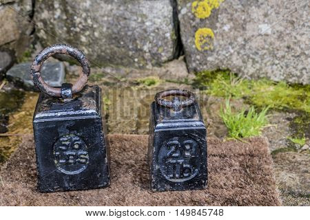Pair of heavy black painted vintage weights inscribed with imperial measurements 56 LBS and 28lb against old lichen covered stone wall.