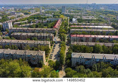Tyumen, Russia - August 18, 2016: Aerial view on sleeping neighborhood large-panel houses, so called KPD. Geologorazvedchikov street. Power plant on background