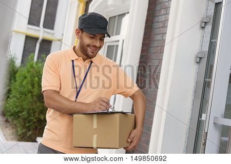 Delivering direct to your door. Smiling courier in uniform holding box and putting signature in clipboard, standing outdoor