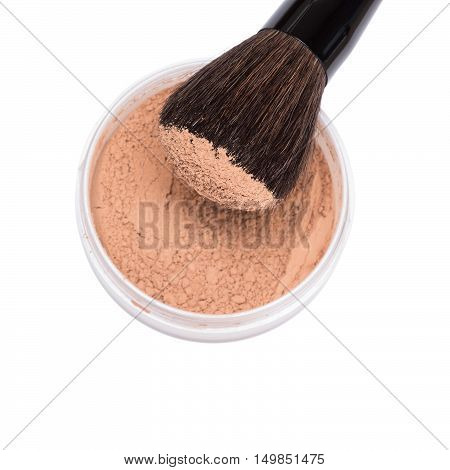 Close-up of makeup brush with jar of loose cosmetic powder isolated on white background. Shallow depth of field, focus on powdery brush bristle