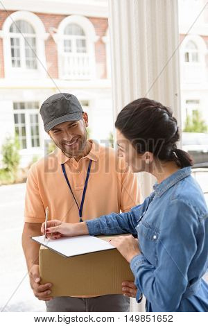 Where I need to sign. Nice deliveryman holding parcel and expressing positivity while giving it to client while putting signature in clipboard