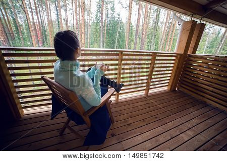 girl in a blue sweater sitting on a wooden chair and drinking tea from a white mug on the veranda of the second floor balcony in the house in the pine forest.