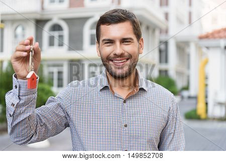 New beginnings. Cropped shot of smiling man standing in front of new house and holding key