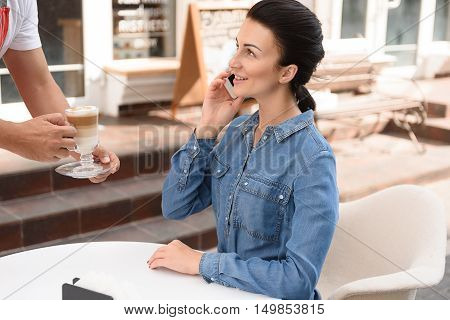 Relaxing with coffee. Beautiful young woman using her smartphone at coffee shop while waiter giving cup of latte