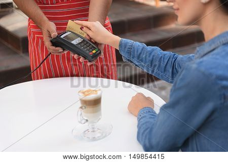 Paying made easy. Cropped shot of young woman paying by credit card in coffee shop, sitting outside