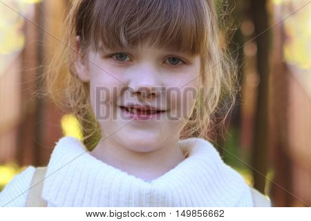 Little beautiful girl in white blouse poses outdoor at sunny summer day