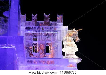 PERM RUSSIA - JAN 4 2016: Illuminated unicorn on wall in Ice town Ice town in Perm - traditional winter attraction